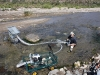 Ray using a dredge in a riverbed under the rocks